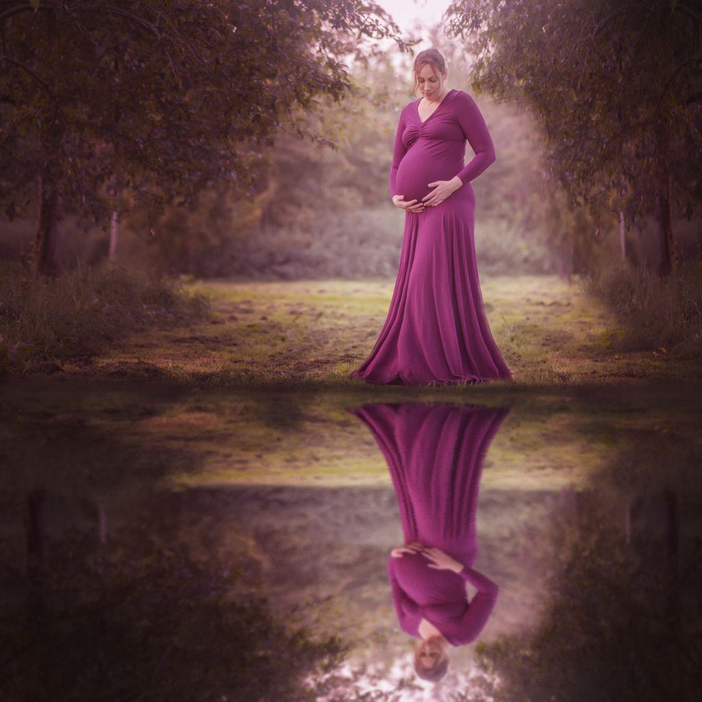 Zwangerschapsfotoshoot in Assen drenthe groningen friesland met reflectie in het water in mooie zwangerschapsjurk
