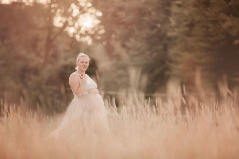 Zwangerschapsshoot in Drenthe Groningen Friesland tijdens zonsondergang in Assen in mooie jurk