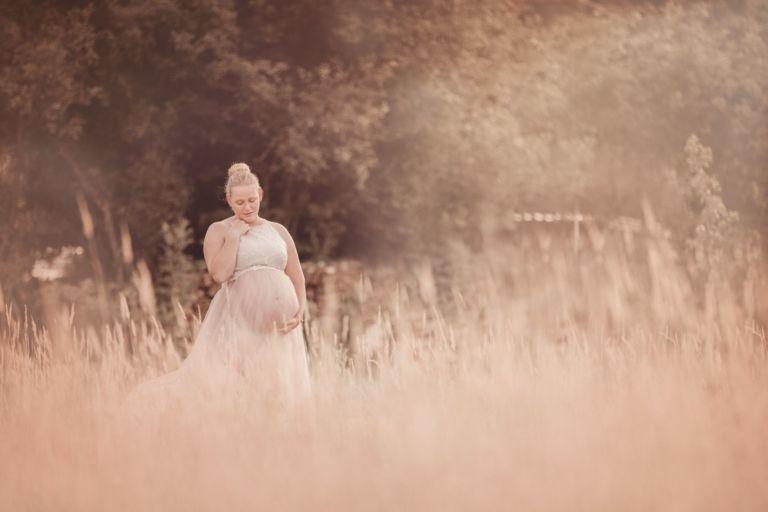 Zwangerschapsshoot en zwangerschapsfoto's door fotograaf uit Assen Drenthe Friesland en Groningen tijdens zonsondergang in mooie zwangerschapsjurken
